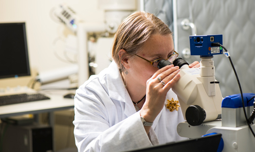 White coated researcher peering into microscope in lab