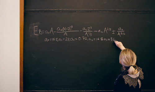 Lecturer writing equation on blackboard