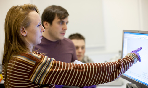 Female research supervisor pointing at a computer screen while two male researchers look on