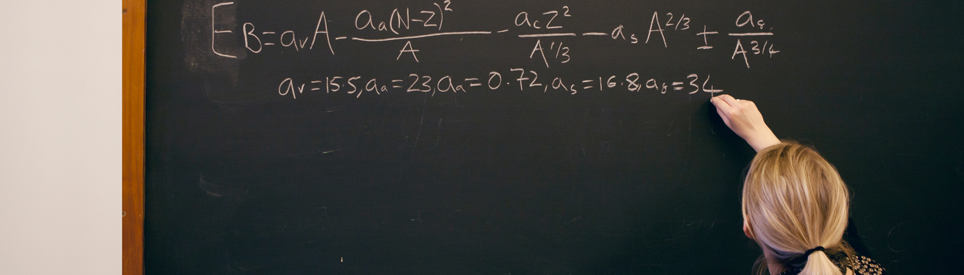 Blonde haired lecturer writing equation on blackboard