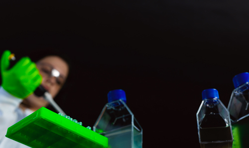 Worm's eye view of researcher squeezing pipette into bottle